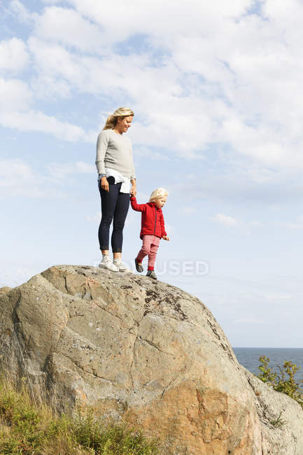 Woman standing with son on rock under sky with clouds — Stock Photo