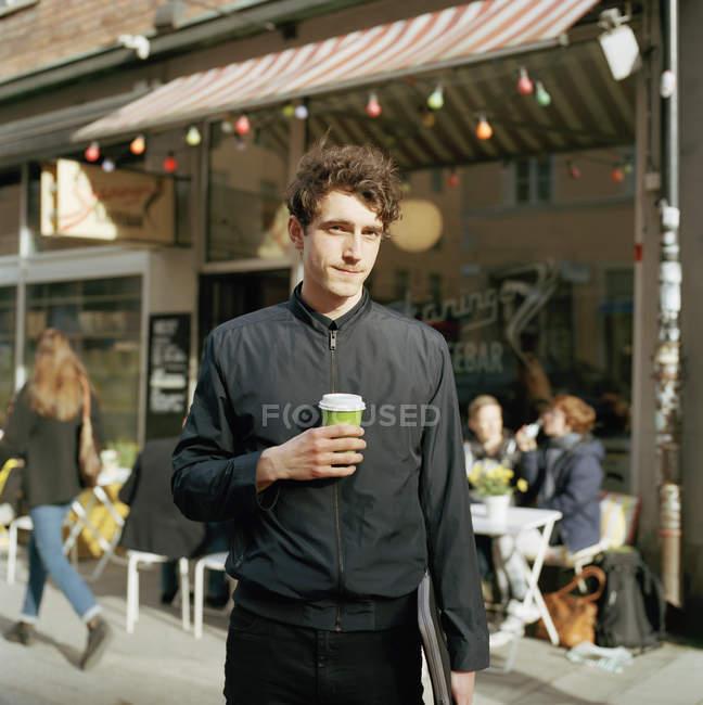 Чоловік, що стоїть на вулиці з ноутбуком і одноразові Кубок в руці — стокове фото