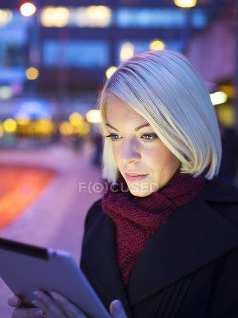 Woman using digital tablet in evening lights — Stock Photo