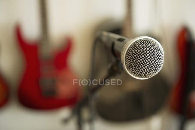 Крупный план микрофона и обезвреженных гитар на заднем плане — стоковое фото