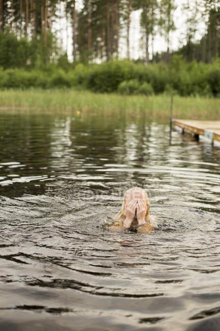 Menina no lago secando os olhos com as mãos, foco seletivo — Fotografia de Stock