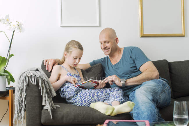 Father doing homework with daughter at living room — Stock Photo