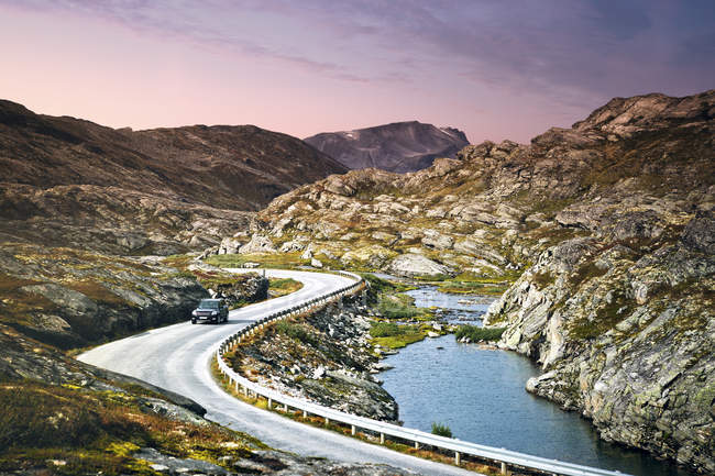 Voiture le long de la route des trolls d'enroulement à côté de l'étroit fjord — Photo de stock