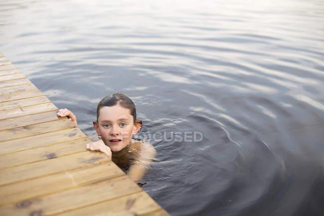 Vue de face de garçon dans le lac touchant jetée en bois — Photo de stock