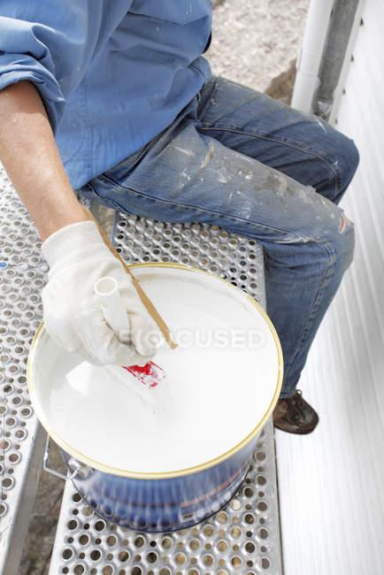 Low section of senior man putting paintbrush into bucket — Stock Photo