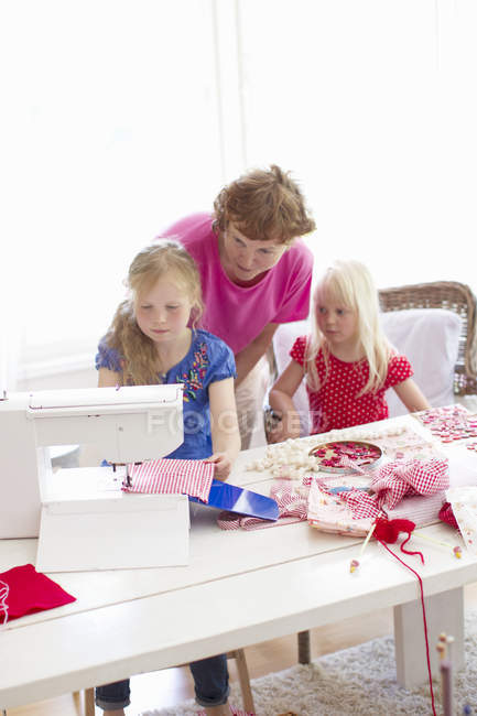 Grandmother with two granddaughters playing with sewing machine — Stock Photo