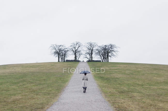 Rear view of woman with umbrella at Woodland Cemetery — Stock Photo