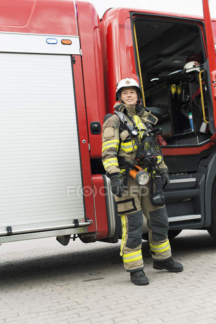 Female firefighter in uniform standing by fire engine — Stock Photo