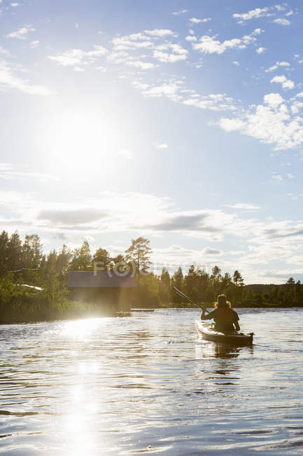 Rear view of mid adult man in canoe — Stock Photo