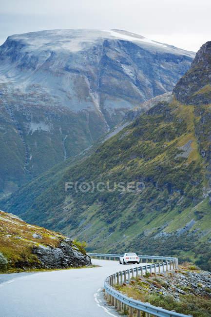 Voiture le long de la route des trolls, serpentant dans la vallée de montagne — Photo de stock