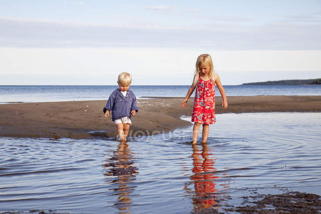 Boy and girl playing in water at beach — Stock Photo