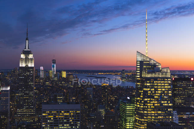 Illuminated manhattan skyscrapers under cloudy sunset sky — Stock Photo
