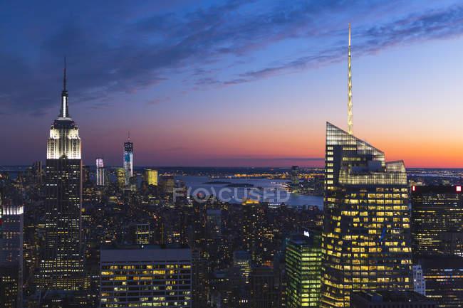 Arranha-céus iluminados Manhattan sob céu nublado por sol — Fotografia de Stock