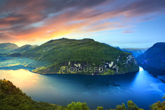 View of lake and mountains under sunrise sky — Stock Photo