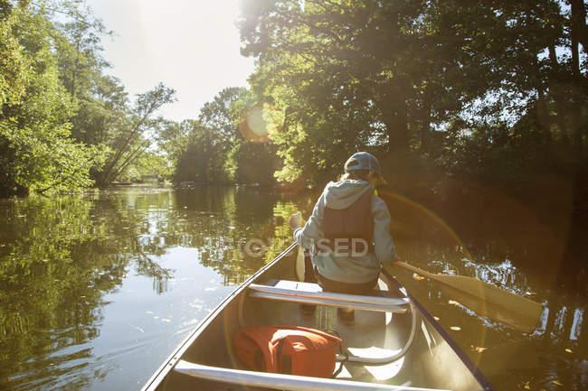 Vue arrière du garçon à la casquette de baseball assis en canoë — Photo de stock