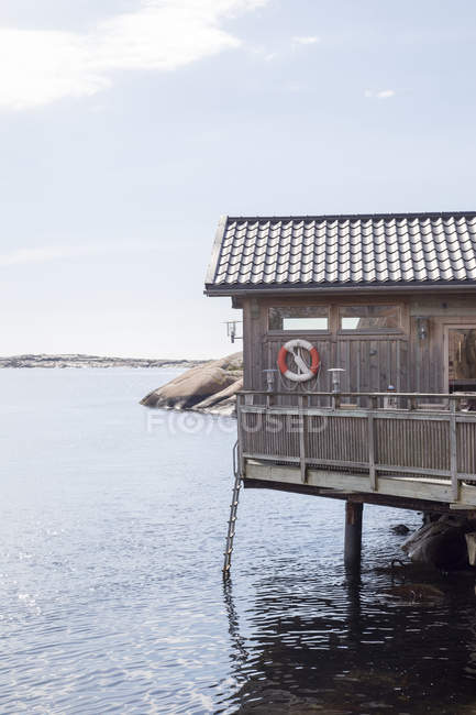 Wooden hut with lifebelt on wall over sea — Stock Photo