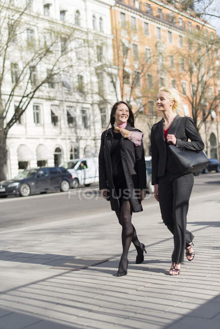 Dos mujeres caminando en la calle, se centran en primer plano - foto de stock