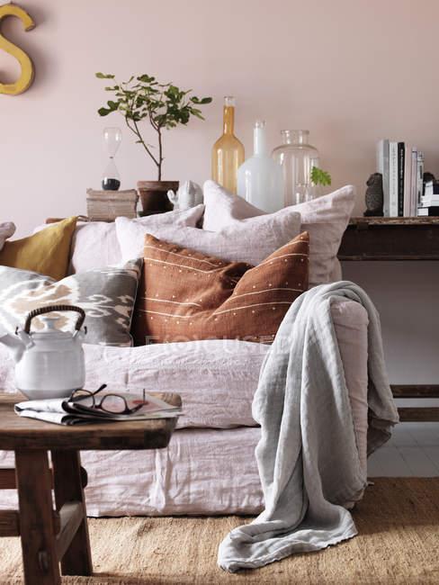 Modo de exibição tabela sofá e diário com o bule de chá na sala de estar — Fotografia de Stock
