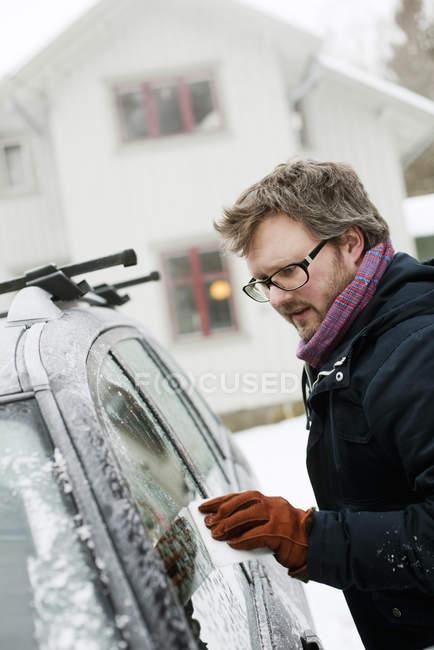 Mann kratzt im Winter Eis von Autoscheibe — Stockfoto