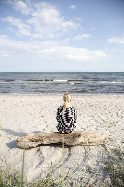Mature woman sitting on driftwood and looking at sea — Stock Photo