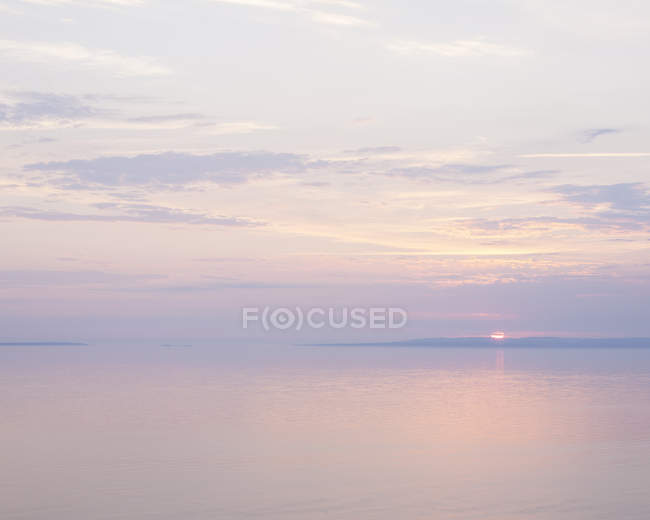 Scenic view of sunset seascape under cloudy sky — Stock Photo