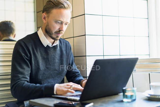 Médio empresário adulto trabalhando no laptop no café — Fotografia de Stock