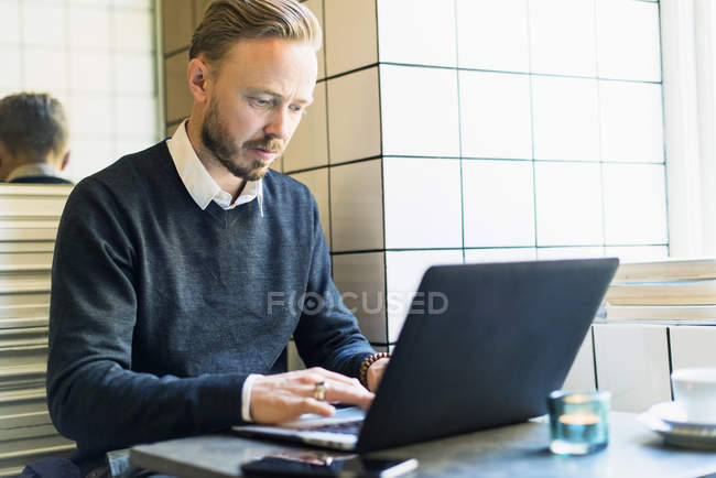 Mid adult businessman working on laptop in cafe — Stock Photo