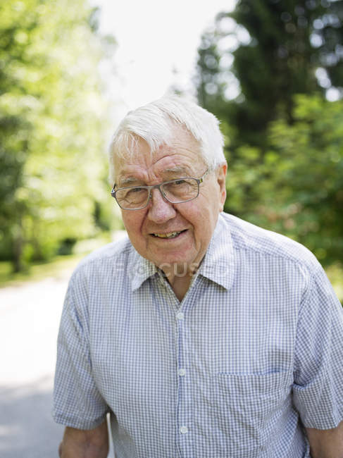 Portrait of senior man wearing shirt and spectacles — Stock Photo