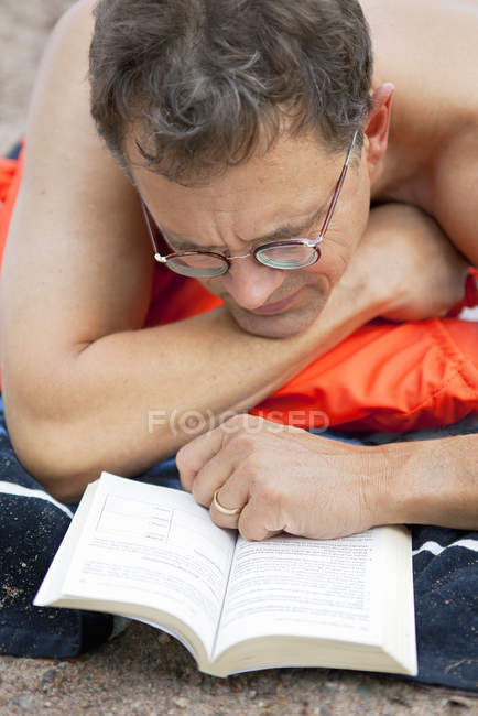 Elevated view of man lying on beach and reading book — Stock Photo