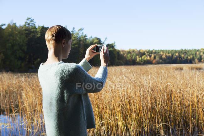 Задний вид женщины, фотографирующей водно-болотные угодья — стоковое фото