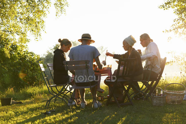 Family having dinner in backyard at sunset — Foto stock