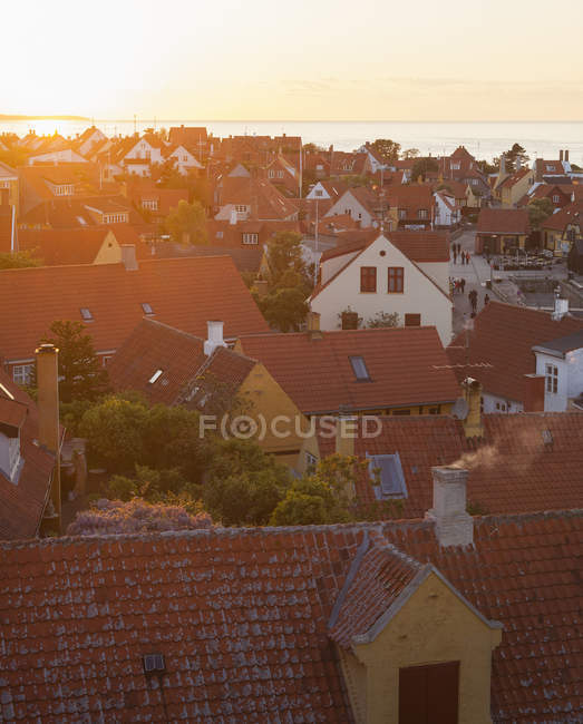 Town buildings roofs with sea in sunlight — Stock Photo