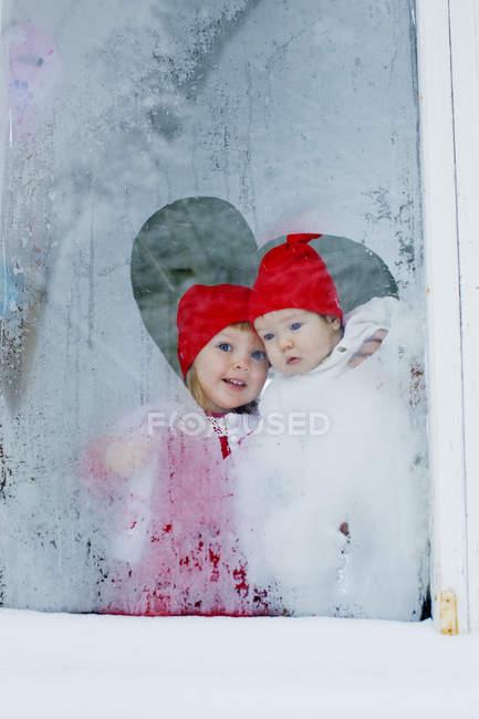Sorelle che osservano fuori finestra smerigliato, fuoco selettivo — Foto stock