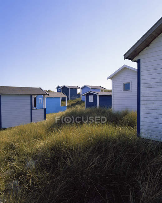 Барвисті Хатки на трав'янистих пляж під Синє небо — стокове фото