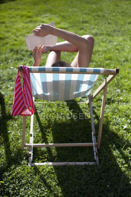 Задний вид женщины, расслабляющейся в шезлонге — стоковое фото