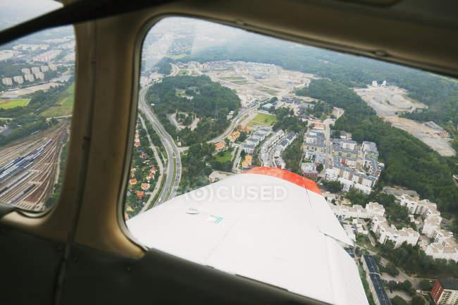 Vista em terra com edifícios através da janela do avião — Fotografia de Stock