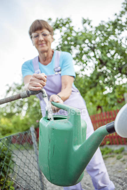 Woman filling watering can in garden — Stock Photo