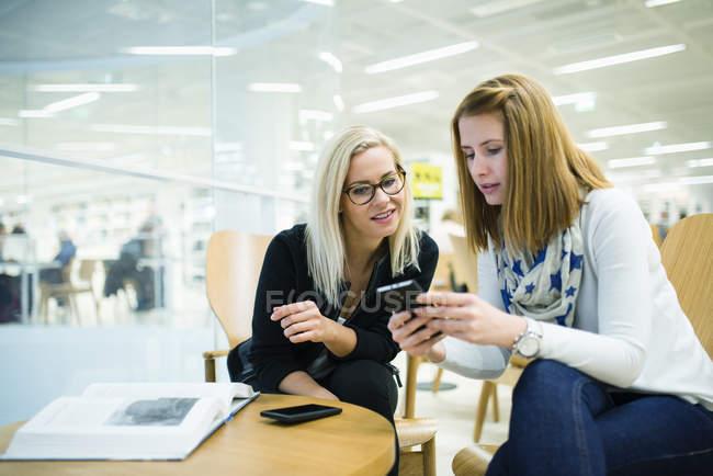 Duas mulheres usando telefone inteligente no escritório, foco diferencial — Fotografia de Stock