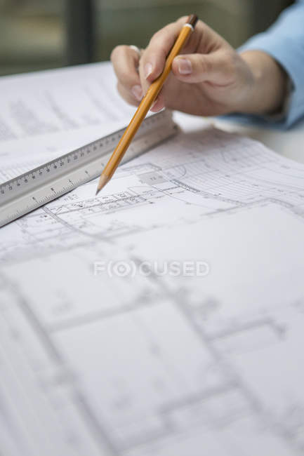 Female hand holding pencil over blueprint — Stock Photo