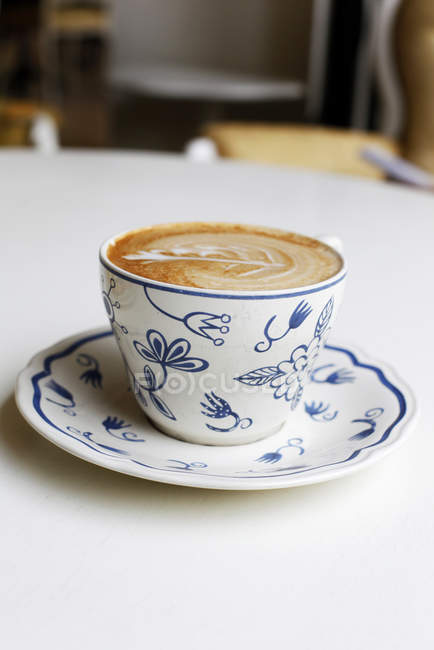 Cup of cappuccino coffee on white table — Stock Photo