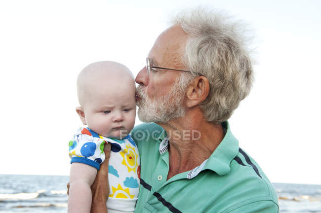 Man holding and kissing grandson, focus on foreground — Stock Photo