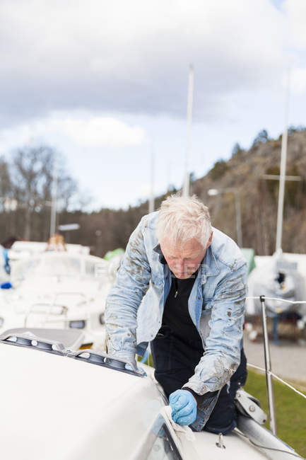 Man maintaining sailboat, focus on foreground — Stock Photo