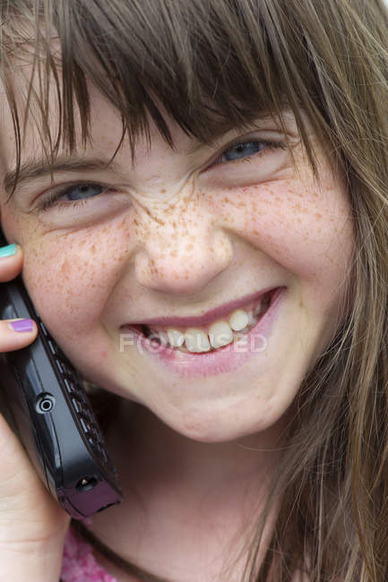 Front view of happy girl using mobile phone — Stock Photo