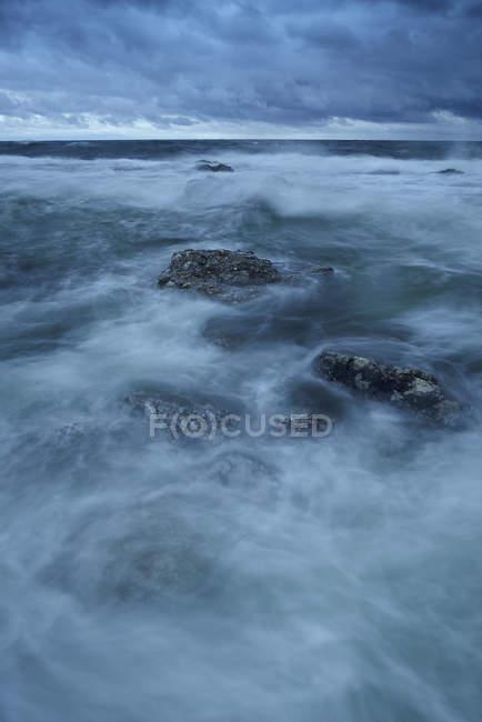 Cielo coperto sulla costa rocciosa con onde sfocate — Foto stock