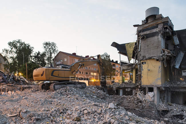 Crane and demolished building in evening light — Stock Photo