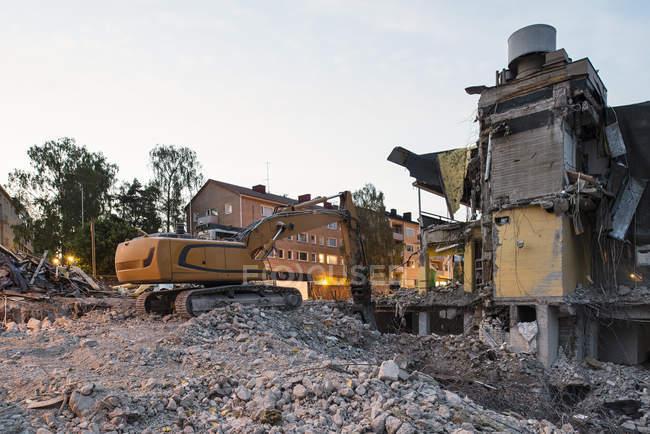 Grúa y demolido edificio en la luz del atardecer - foto de stock