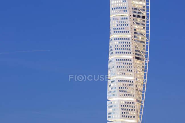Grattacielo illuminato contro il cielo blu — Foto stock