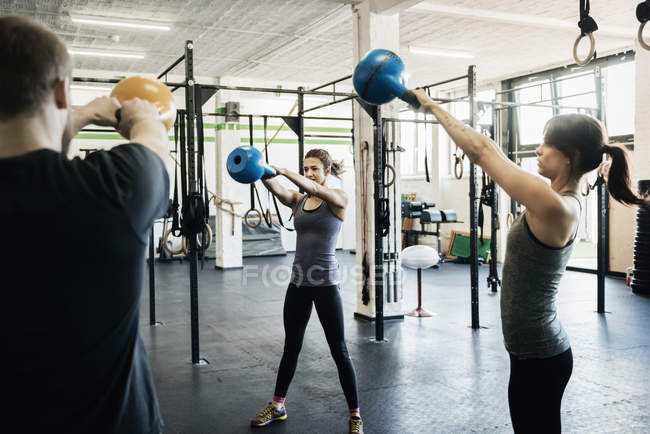 Young women and man swinging kettlebells in gym — Stock Photo