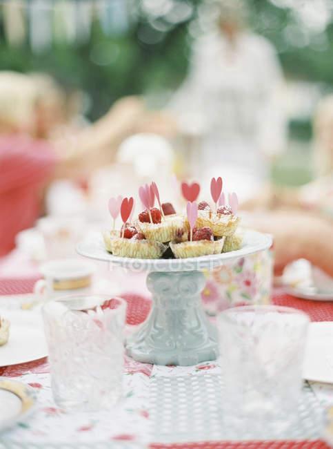 Muffins auf Kuchen stehen mit herzförmigen Dekorationen — Stockfoto