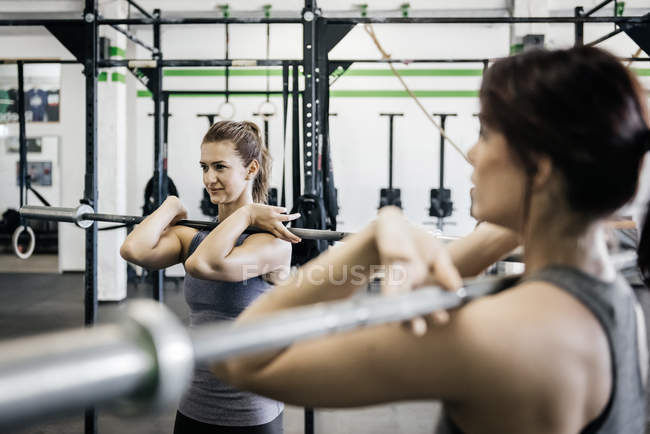 Levantamiento de pesas de dos mujeres jóvenes en el gimnasio - foto de stock